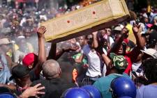 Fees2017 protesters fling a coffin symbolising Blade Nzimandes coffin into a police barricade outside parliament. Picture: Anthony Molyneaux/EWN