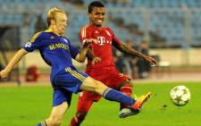 BATE Borisov's Aleksandr Pavlov (L) fights for the ball against Bayern Munich's Luiz Gustavo (R) during on their Champions League Group F soccer match in Minsk, on 2 October, 2012. Picture: AFP.