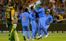 India's captain Mahendra Singh Dhoni (2nd R) celebrates with teammates after running out South Africia's AB de Villiers on February 22, 2015. Picture: AFP