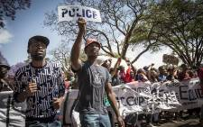FILE: A student holds up a police label in front of demonstrating students during protests over tertiary education fees in Pretoria on 10 October 2016. Picture: Reinart Toerien/EWN.