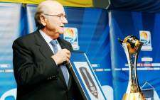FILE: Fifa President Sepp Blatter shows the Fifa Club World Cup trophy (R) and a certificate for the champion of the Fifa Club World Cup after of a news conference in Tokyo, Japan, 15 December 2012. Picture: EPA.