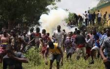 People run from tear gas shot by Nigerian police officers during a mass looting of a warehouse that had COVID-19 food palliatives that were not given during lockdown to relieve people of hunger, in Abuja, Nigeria, on 26 October 2020. Picture: AFP