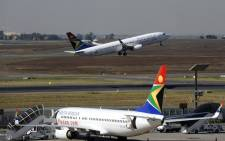 An SAA flight takes off as another one is parked in a bay on the tarmac at the Johannesburg OR Tambo International Airport. Picture: AFP