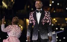FILE: Pastor Shepherd Bushiri (R), also known as Prophet Bushiri from the Enlightened Christian Gathering (ECG), stands on stage while his wife, Mary Bushiri, speaks to worshippers during the United Prayers Crossover at the FNB Stadium in Soweto on 1 January 2020. Picture: AFP