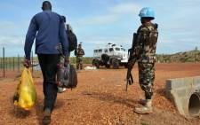 FILE: A South Sudanese man walks past UN peacekeepers on 17 September 2014 in Juba. Picture: AFP.