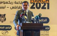 Libya's interim prime minister Abdul Hamid Dbeibah (L C) delivers a speech at a national conference on the COVID-19 pandemic, at a conference hall in the capital Tripoli, on March 13, 2021. Picture: Mahmud Turkia / AFP.