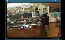 YouTube screengrab of Said Ahmed, owner of the Egyptian Kebab House in New Zealand, ignoring a would-be robber.
