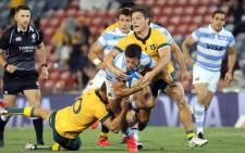 Australia's Reece Hodge (L) and Australia's captain Michael Hooper (R) tackle Argentina's Bautista Delguy (C) during the 2020 Tri Nations rugby match at McDonald Jones Stadium in Newcastle on 21 November 2020. Picture: AFP