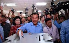 Cambodia's Prime Minister Hun Sen casts his vote during the general elections as his wife Bun Rany (centre L) looks on in Phnom Penh on 29 July, 2018. Picture: AFP.