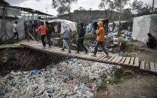 FILE: Children walk over a bridge in the Moria migrant camp on the Greek Aegean island of Lesbos on March 5, 2020. Picture: AFP