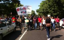 Protesters walk along main road, halting traffic briefly before turning up to lower campus again. Police presence remains. Picture: Anthony Molyneaux/EWN.