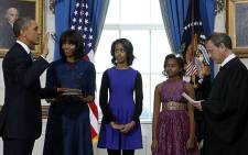 US President Barack Obama (L) takes the oath of office from US Supreme Court Chief Justice John Roberts (R) as first lady Michelle Obama holds the bible and daughters Malia (3rd L) and Sasha look on in the Blue Room of the White House in Washington on January 20, 2013. Picture: AFP.