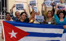 Cubans celebrate with a national flag in Camaguey, 600 km east of Havana on 17 December, 2014, to celebrate after Washington released three Cuban spies who had been in a US prison since 2001. Picture: AFP.