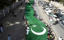 Pakistani residents carry a huge flag during a rally to mark the country's Independence Day in Quetta on 14 August 2017. Picture: AFP