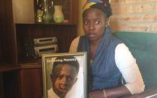 The mother of Siyabonga Ngxesha holds up a picture of her deceased 14-year-old son. Picture: Vumani Mkhize/EWN.