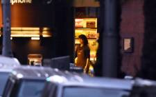 A female hostage stands by the front entrance of the cafe as she turns the lights off in the Sydney central business district on 15 December, 2014. Picture: AFP.