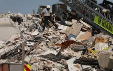 A Miami-Dade Fire Rescue person and a K-9 continue the search and rescue operations in the partially collapsed 12-story Champlain Towers South condo building on 24 June 2021 in Surfside, Florida. Picture: JOE RAEDLE/AFP
