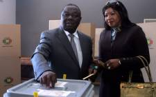 Zimbabwe's Prime minister, leader and candidate of the Movement for Democratic Change (MDC), Morgan Tsvangirai (L), flanked by his wife Elizabeth, casts his ballot in a polling station in Harare July 31, 2013, to vote in a general election. Picture: AFP.