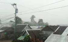 This handout image taken and received on 2 December 2019 courtesy of Gladys Vidal shows heavy rains and moderate wind from Typhoon Kammuri battering houses in Gamay town, Northern Samar province. Picture: AFP.