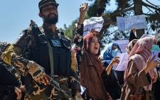Afghan women shout slogans next to a Taliban fighter during an anti-Pakistan demonstration near the Pakistan embassy in Kabul on 7 September 2021. Picture: Hoshang Hashimi/AFP