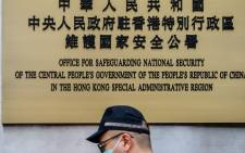 A police officer walks past a plaque outside the Office for Safeguarding National Security of the Central People's Government in the Hong Kong Special Administrative Region after its official inauguration in Hong Kong on 8 July 2020. Picture: AFP