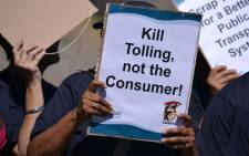 A protester holds up a placard voicing their message against e-tolling. Picture: Aletta Gardner/EWN