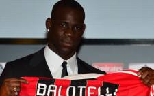 New AC Milan player, Italian striker Mario Balotelli, poses with his team's jersey prior a press conference on February 1, 2013 at San Siro Stadium in Milan. Picture: AFP/ Giuseppe Cacaces