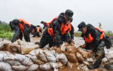 This photo taken on 15 July 2020 shows China's paramilitary police officers placing sandbags on a levee in the rain near the Yangtze River in Tongling in China's eastern Anhui province. Picture: AFP