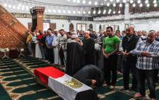 Egyptians pray before the coffin of police officer Ahmed Fayez during his funeral inside a mosque in the capital Cairo's western suburb of Sixth of October on 21 October 2017. Picture: AFP.