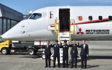 Mitsubishi Aircraft Corporation president Hiromichi Morimoto (L), chief test pilot Yoshiyuki Yasumura (2nd L), test pilot Kazuo Toda (C), and guests pose with Japan's first domestically produced passenger jet, the Mitsubishi Regional Jet (MRJ), at Nagoya airport in Komaki, Aichi prefecture on 11 November, 2015 following the aircraft's maiden test flight. Picture: AFP.