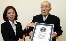 Japan's oldest man Sakari Momoi receiving a certificate naming him as the world's oldest man by the Guinness World Records at a hospital in Tokyo on 20 August, 2014. Picture: AFP.