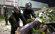 Paramilitary police officers clean up damaged trees and branches on road after super Typhoon Mangkhut in Zhongshan, south China's Guangdong province early on 17 September, 2018. Picture: AFP