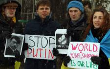 """Demonstrators hold placards reading """"World- your support is our lives"""" and """"Stop Putin"""" during a protest against Russia's intervention in Ukraine on 16 March 2014. Picture: AFP."""
