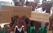 "Pupils holding up message of ""Stop raping children"" during Keabetswe's funeral in Germiston. Picture: Sebabatso Mosamo/EWN."