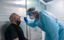 FILE: A passenger is tested by a doctor at a coronavirus screening station in the medical center of the airport in Duesseldorf, western Germany, on 27 July 2020. Picture: AFP.