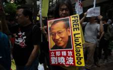 Radical legislator Leung Kwok-hung holds a banner of Chinese dissident Liu Xiaobo during a pro-democracy protest in Hong Kong on 18 May 2016, during the second day of a visit by China's National People's Congress (NPC) Standing Committee Chairman Zhang Dejiang. Picture: AFP