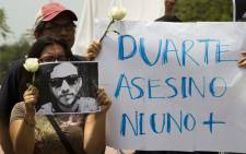 """Mexican photojournalists hold a picture of murdered colleague Ruben Espinosa and a banner reading """"Duarte assassin. Not one more,"""" for Javier Duarte, the governor of Veracruz, during a demonstration in Guadalajara City, on 2 August, 2015. Picture: AFP"""