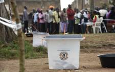 Ballot boxes are pictured as people line up to cast their vote in presidential and parliamentary polls, on 18 February, 2016 at the Nasuti polling station in Mukono District, some 23 kilometres east of the capital Kampala. Picture: AFP.""