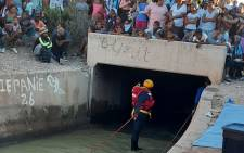 Community members watch as SAPS search and rescue teams search for Rudicia Gelant (9) after she fell into a canal in Dysselsdorp, in the southern Cape, on 3 May 2021. Picture: @SAPoliceService/Twitter
