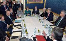 French Foreign Minister Laurent Fabius, (L),the European Union's negotiator Catherine Ashton (C) and US Secretary of State John Kerry (R) and British Foreign Secretary Philip Hammond (bottom) sit at a conference table prior to their talks between the E3 3 (France, Germany, UK, China, Russia, US) and Iran in Vienna, Austria, 21 November 2014. Picture: EPA.