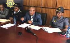 Deputy Police Minister Bongani Mkongi (C) addressing the media at the Hillbrow police station. Picture: Kgothatso Mogale/EWN.