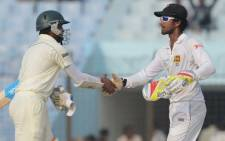 BANGLADESH, Chittagong : Bangladeshi batsman Shakib Al Hasan (L) shakes hands with Sri Lankan wicketkeeper Dinesh Chandimal following the fifth and final day of the second Test match between Bangladesh and Sri Lanka at The Zahur Ahmed Chowdhury Stadium in Chittagong on February 8, 2014. Bangladesh and Sri Lanka's second and final Test ended in a draw in Chittagong, giving the tourists a 1-0 series win. Picture: AFP.