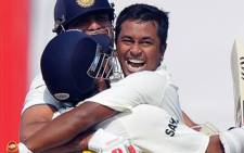 Indian cricketer V.V.S Laxman (C) with Pragyan Ojha (R) and Suresh Raina celebrate India's win over on 5 October 2010. Picture: Dibyangshu Sarkar/AFP