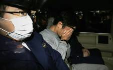 Takahiro Shiraishi covers his face with his hands as he is transported to the prosecutor's office from a police station in Tokyo on 1 November 2017. Picture: AFP.