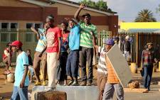 Residents of Bekkersdal in Westonaria in a stand-off with police during a service delivery protest on 24 October 2013. Picture: Sebabatso Mosamo/EWN