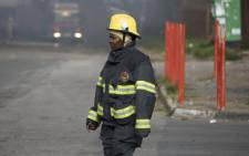 FILE: A firefighter walks by a massive blaze that engulfed the Jumbo Cash & Carry near the M1 Highway in Crown Mines on Thursday 25 Feb 2016. Picture: Christa Eybers/EWN.