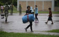 A woman carries her baby at an improvised shelter in Escuinapa, Sinaloa state, Mexico, on 23 October, 2018, before the arrival of Hurricane Willa. Picture: AFP