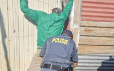 Police search a resident as part of Operation Okae Molao in the Slovo Park informal settlement, west of Johannesburg on 14 May 2020. Picture: @GP_CommSafety/Twitter