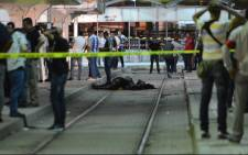 FILE: Onlookers gather at the scene outside a metro station where a man reportedly wearing an explosive belt blew himself up in the early hours of 3 July 2019 in the capital Tunis, after being chased by police. Picture: AFP.