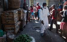 A council worker sprays disinfectant during the clean-up of the market of Anosibe in the Anosibe district, one of the most unsalubrious districts of Antananarivo on 10 October 2017. Picture: AFP.